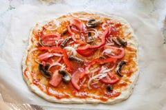 Rohe selbst gemachte Pizza mit Tomaten, Oliven, Gemüsepaprika Stockfoto