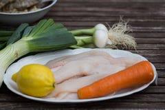 Rohe Sohle auf einer Platte mit Zitrone, Salbei, Karotte, Fisch, frisch, Holztisch, Tabelle Stockbild