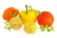 Rohe Teigwaren mit der Tomate, Pfeffern und Grüns getrennt Lizenzfreie Stockbilder