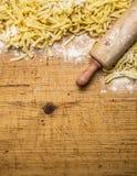 Rohe Teigwaren mit Mehl und einer Nudelholzgrenze, Platz für Draufsichtabschluß des Hintergrundes des Textes hölzernen rustikalen Stockbild