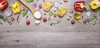 Rohe Teigwaren mit Pfeffern und Kirschtomaten mit einem hölzernen Löffel und einem Salz auf einem langen grauen hölzernen Draufsi Lizenzfreies Stockfoto