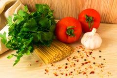 Rohe Teigwaren mit Tomaten und Gewürze und Kräuter auf dem Tisch stockbild