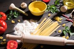 Rohe Teigwaren, Tomaten, Pilze, Mehl und Eier auf schwarzem Holztischhintergrund, Draufsicht lizenzfreie stockfotos