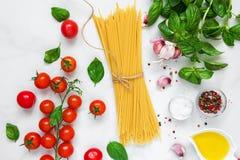 Rohe Teigwarenspaghettis mit Tomaten, Knoblauch und Basilikum auf weißem Marmorhintergrund Kochen des Konzeptes Beschneidungspfad Lizenzfreie Stockbilder