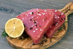 Rohe Thunfischleiste mit Dill, Zitrone und Pfeffern in olivgrünem Schnittbo Stockbild