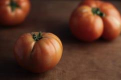 Rohe Tomaten auf einem hölzernen Hintergrund Lizenzfreie Stockfotos