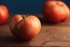 Rohe Tomaten auf einem hölzernen Hintergrund Stockfoto