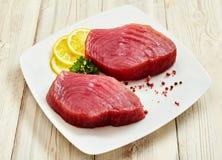 Rohe Tuna Steaks mit Zitrone, Kräutern und Pfefferkörnern Stockfoto