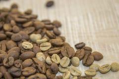 Rohe und Röstkaffeebohnen auf einem Holzfuß Stockfotos