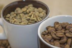 Rohe und Röstkaffeebohnen in einer Schale Stockfoto