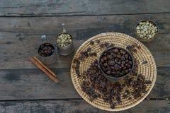 Rohe und Röstkaffeebohnen mit Messingschale auf hölzerner Tabelle Stockbild