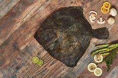 Rohe ungekochte Plattfische auf Holztisch Stockbilder