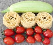 Rohe ungekochte Teigwaren, Gemüse auf grauem Leinen Lizenzfreie Stockfotos