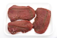 Rohe winzige Steaks auf Servierplatte Stockbilder