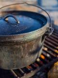 Roheisen-Schmortopf über Lagerfeuer stockbilder