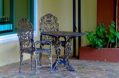 Roheisentabelle und -stühle im Garten Stockbilder