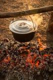 Roheisentopf auf den brennenden Klotz des Feuers Stockfoto