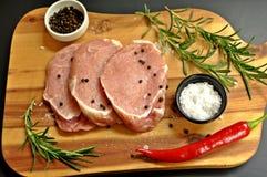 Roher frischer ungekochter geschnittener Schweinefleisch-Leistenteller mit Rosmarin, Pfeffer, Salz, Pfeffer des roten Paprikas un stockfotografie
