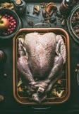 Roher ganzer Truthahn angefüllt mit Trockenfrüchten und Äpfeln in der Bratwanne auf dunklem Küchentischhintergrund, Draufsicht ko stockfotografie