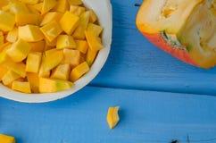 Roher geschnittener Kürbis des Herbstes auf blauem hölzernem Hintergrund Lizenzfreie Stockfotografie