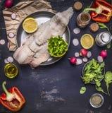 Roher Kabeljau auf Wannenrettichen mit Butter und Jahreszeit mit Draufsicht des dunkelblauen rustikalen hölzernen Hintergrundes d Stockbilder