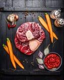 Roher Kalbfleischschaft schneidet Fleisch und Bestandteile für Osso Buco, das auf schwarzem hölzernem Hintergrund kocht Stockbild