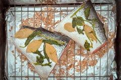 Roher Lachs mit Basilikum und Lorbeer verlässt liegend auf einem Gitter auf einem Räucherhaus kochfertig Lizenzfreie Stockfotos