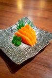 Roher Lachssashimi auf schwarzem japanischem traditionellem Teller auf Holztisch lizenzfreies stockfoto