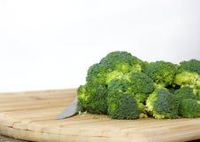 Roher organischer Brokkoli auf einem hölzernen Schneidebrett stockfotos
