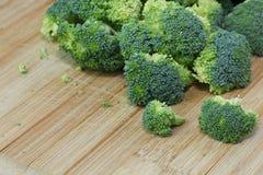 Roher organischer Brokkoli auf einem hölzernen Schneidebrett lizenzfreie stockfotografie