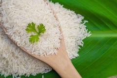 Roher Reis des thailändischen Jasmins auf Draufsicht des grünen Blattes und des hölzernen Löffels Stockfotos