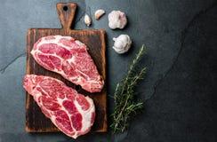 Roher Schweinefleischkoteletthieb für Grill BBQ mit Kräutern auf hölzernem Brett, Schieferhintergrund, Draufsicht, Kopienräume stockfoto
