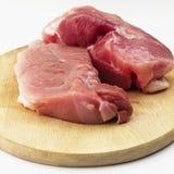Roher Schweinefleischschinken auf hölzernem Schneidebrett auf weißem Hintergrund Stockbild