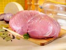 Roher Schweinefleischschinken auf Küchenschneidebrett mit Glasbackform Stockbilder