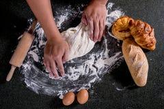 Roher Teig für Brot mit Bestandteilen auf schwarzem Hintergrund, Mann h lizenzfreie stockfotos
