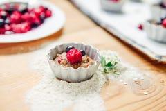 Roher Teig mit Beeren für kleine Kuchen zerlegte in Formen auf einem Backen papper auf Backblech verzierten ewith Blumen Selektiv Stockfotografie