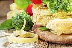 Roher Teigwaren Fettuccine, frischer Brokkoli, grüner Basilikum verlässt, roter ch stockbild