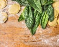 Roher Tortellini mit grünem Spinat verlässt auf hölzernem Hintergrund mit Weizenmehl, Draufsicht Lizenzfreies Stockfoto