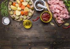 Roher Truthahn mit Tomatensauce, Pfeffer, Gewürze, Krautbestandteile für Eintopfgericht auf hölzernem rustikalem Draufsichtabschl Stockbild