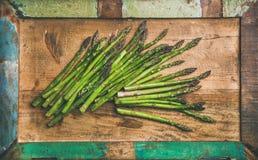 Roher ungekochter grüner Spargel über rustikalem Hintergrund, horizontale Zusammensetzung Stockfoto