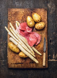 Roher weißer Spargel mit Kalbfleischfleischleiste und Kartoffeln, Vorbereitung auf rustikales hölzernes Schneidebrett, Traditions Lizenzfreie Stockfotos