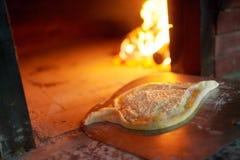 Rohes Ajarian-khachapuri kochte in einem Ofen mit brennendem Brennholz Lizenzfreie Stockfotografie