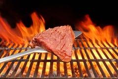Rohes Beefsteak auf dem Blatt über einem heißen BBQ-Grill Stockbilder