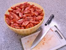 Rohes Bild von gehackten Tomaten in der Schüssel mit dem Hacken der Platte und des großen Messers auf dem granit Küchentisch Lizenzfreies Stockfoto