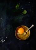 Rohes Ei in einer Schüssel, Löffel, Basilikum auf einem schwarzen Hintergrund Stockbild