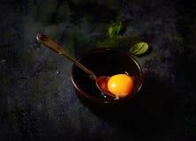 Rohes Ei in einer Schüssel, Löffel, Basilikum auf einem schwarzen Hintergrund Lizenzfreie Stockfotos