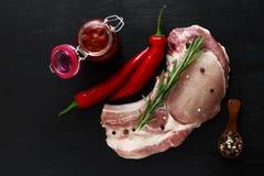 Rohes Fleisch der Schweinefleischmittelrippe vom rind mit Rosmarin, Pfeffer und roter Soße Lizenzfreie Stockfotos