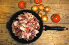 Rohes Fleisch in einer Bratpfanne mit Zwiebel und Tomaten lizenzfreie stockbilder