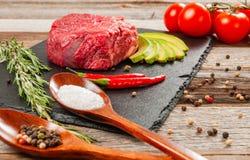 Rohes Fleisch, Rindfleisch mit Gewürzen für das Kochen auf schwarzem Brett stockbild