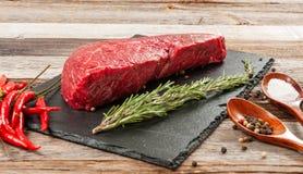 Rohes Fleisch, Rindfleisch mit Gewürzen für das Kochen auf schwarzem Brett lizenzfreies stockfoto